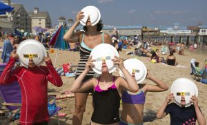 OLD ORCHARD BEACH - AUGUST 21: Members of two vacationing families observe the partial solar eclipse through some hand-improved solar glasses at Old Orchard