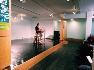 A picture of Megan Grumbling reading one of her poems aloud at the library.