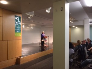 An image of Sally Woolf-Wade reading a poem out loud in front of an audience.