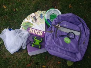 Purple backpack on the grass with the following contents surrounding it: butterfly net, binoculars, magnifying glass, two way bug viewer, insect habitat, clipboard case.