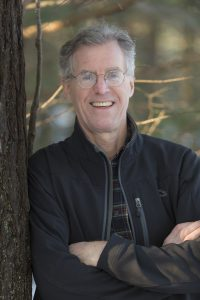picture of the male author smiling, with arms crossed leaning against a tree