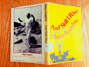 """A photograph of a yellow book called """"And Still I Rise,"""" open so that it shows picture of the author, Maya Angelou, on the back cover."""