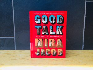 A picture of the book Good Talk by Mira Jacob. It is a red book with illustrations on the cover depicting the author as a child, teenager, and adult.