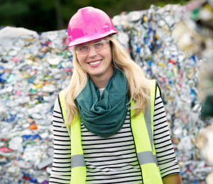 Blonde woman standing in front of a landfill wearing a safety vest, safety glasses, and pink hard hat.
