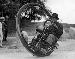 Vintage portrait of a man riding a one wheel motor cycle